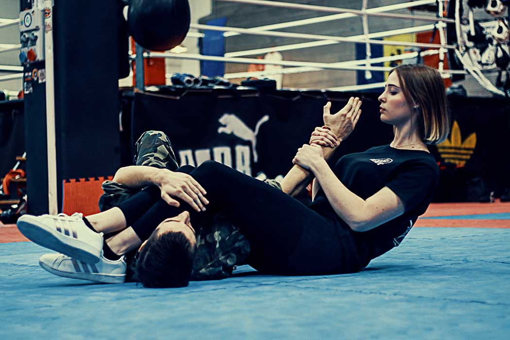 blonde girl doing armbar on the ground